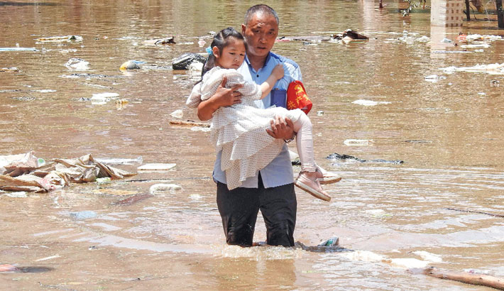 A village official evacuates a child from a flooded area following heavy rains in Dazhou in China's southwestern Sichuan province. The photo was taken on Monday. – AFPPHOTO