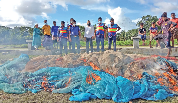 Members of Coast Guard Bangladesh burn huge banned current nets seized from different areas of Andharmanik River under Kalapara Upazila of Patuakhali district on Tuesday.— Star Mail
