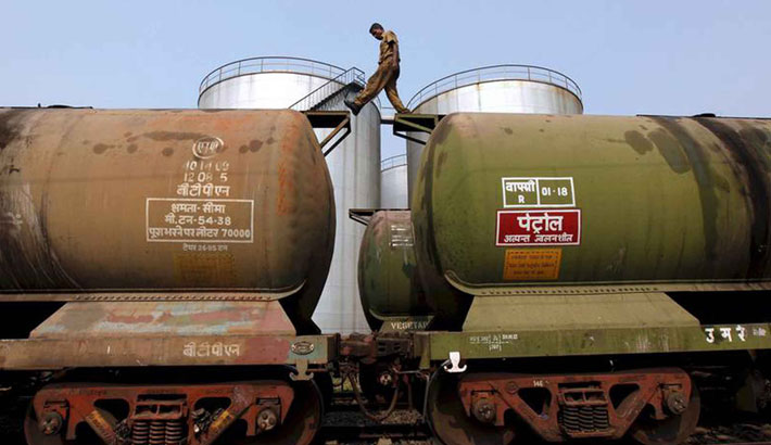A worker walks atop oil tanker wagons at an oil terminal near Kolkata, India. The stalemate within the world's main oil-exporting bloc has left traders uncertain about future supply.