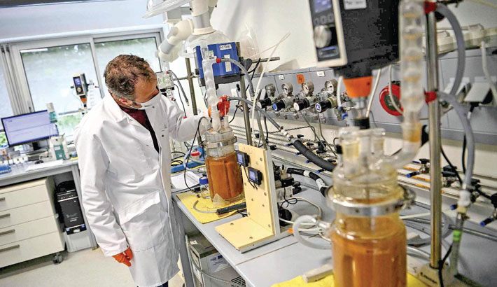 A technician fills vials with a liquid solution to separate rare earths (terres rares) from mining waste at the Bureau de Recherches Geologiques et Minieres (BRGM) (Geological and Mining Research Office) in Orleans, central France.