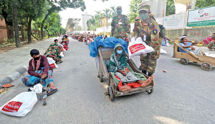 Army men distribute food items and other humanitarian aid among the destitute hit hard by the coronavirus pandemic in Dhaka University area on Thursday. — SUN photo