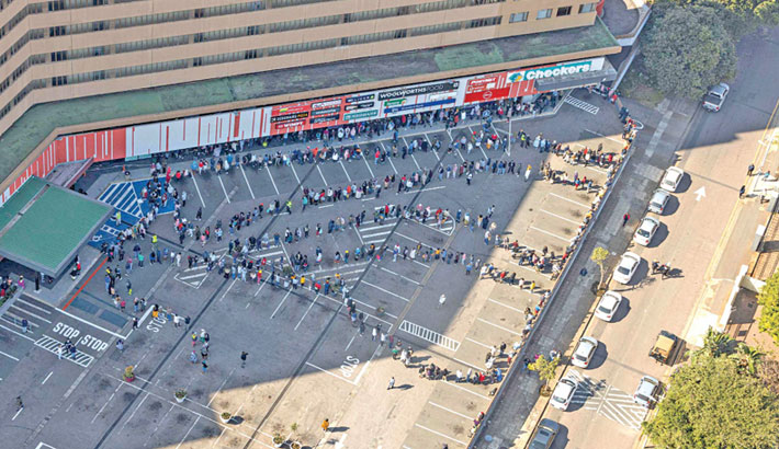 This aerial view shows people queueing to buy food and other supplies at the Windermere Shopping Centre in Durban on Friday. Hundreds of people have been forced to queue outside grocery stores across Durban as only a handful of retailers remain open after the unrest that has affected the country has led to a shortage of food and supplies in many areas.
