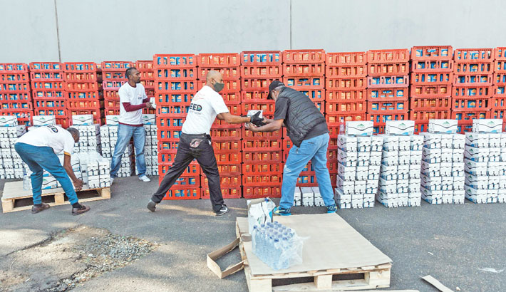 A photograph taken on Saturday shows a volunteer from Muslims For Humanity offloads a crate of bread and milk at the NMJ Islamic Centre to distribute to members of the public in Durban. After a week of incidents in South Africa, marked by riots and looting, a precarious calm seems to hang over the country on Saturday which continues to clean up the damage of violence described by President Ramaphosa as an orchestrated attempt to destabilize the country.