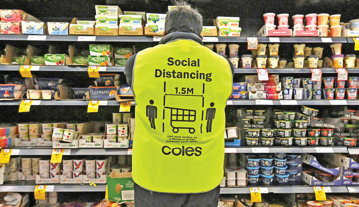 A supermarket worker with a social distancing message on his uniform stocks shelves at a shopping centre in Sydney on Saturday, as authorities ordered new restrictions as a weeks-long lockdown failed to quash an outbreak of the Covid-19 coronavirus.