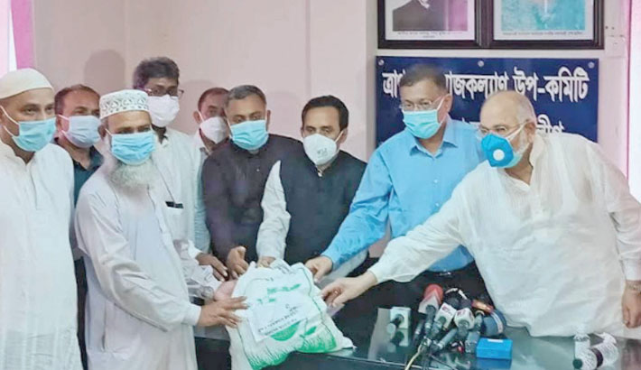 Information and Broadcasting Minister Dr Hasan Mahmud hands over Eid gifts and health protection materials to the representatives of different organisations at Awami League president's political office in the city's Dhanmondi area on Monday.  —SUN PHOTO