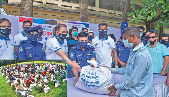 Rotary Club of Bogura President Syed Ahammad Kiron and Police Super Ali Ashraf Bhuiyan hands over sack of relief materials to lockdown-hit poor people at Zila School field in the district town on Monday. — Monirul Islam Maruf