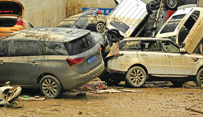 Damaged vehicles stacked on each other are seen in a car park following heavy rain which caused flooding earlier in the week that claimed at least 56 lives, in the city of Zhengzhou in China's Henan province on Saturday. —AFP PHOTO