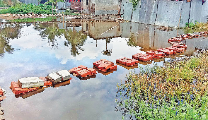 Over 100 families have been left marooned in Uttar Lalpur and Jautdaibaki areas of Lalpur upazila in Natore district for over a month due to clogged drainage system there   -  Sun Photo