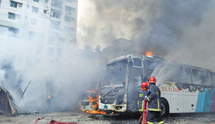 Firefighters spray water to douse a blaze at a motor garage in the capital's Motijheel area on Sunday. At least two buses of a private transport company were gutted in the fire. —Md Nasir Uddin