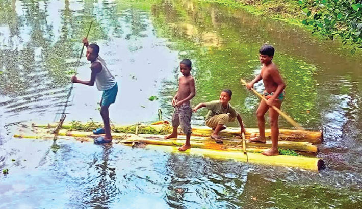 Four playful boys are rafting in a pond to have fun at Borobila village in Dhunat Upazila of Bogura district on Monday.—sun photo