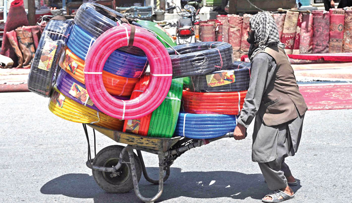 A man pushes a wheelbarrow loaded with plastic water pipes along a road in Kabul on Tuesday.