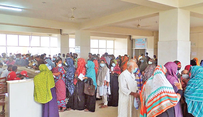 Without maintaining social distancing guidelines, hundreds of people are waiting in a queue in front of corona vaccination centre in Jhenaidah District Hospital to receive corona vaccine. The photo was taken on Wednesday. – Sun Photo