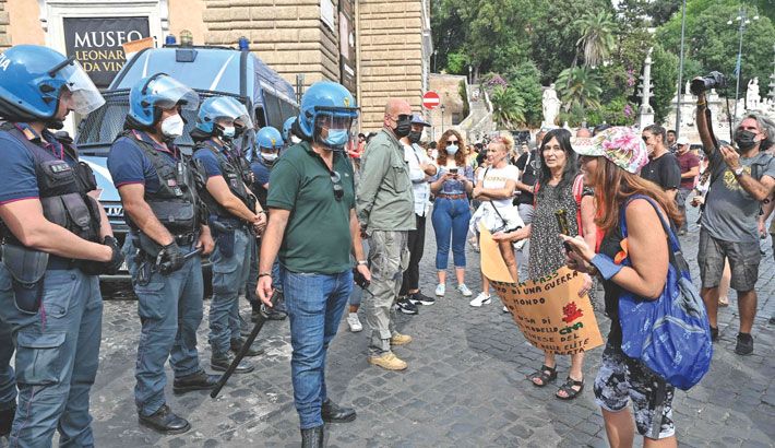 Protestors face riot police officers during a demonstration against the introduction of a mandatory