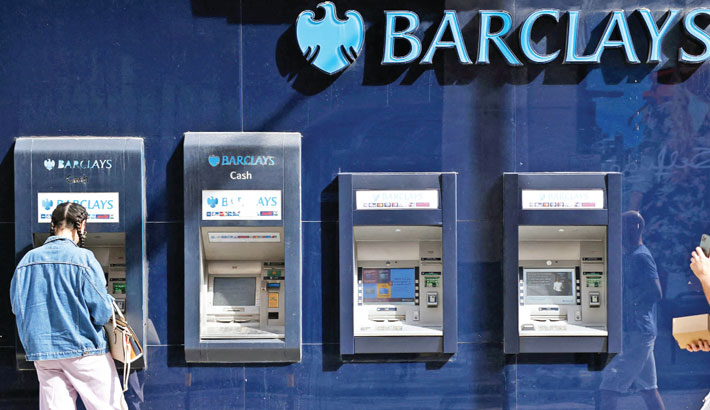 A pedestrian (R) walks past a row of ATMs as a customer uses one outside a branch of British bank Barclays in central London on Wednesday. British bank Barclays said Wednesday that first-half net profits surged on lower-than-expected credit losses, as the global economy shows signs of recovery from the pandemic.