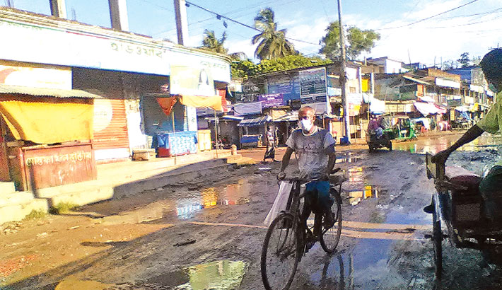Naogaon-Badalgachhi-Nozirpur road lies in a dilapidated condition with numerous potholes and ditches making it almost unfit for traffic, but the authorities concerned seemed to be indifferent to the problem. The photo was on Monday. – Sun Photo
