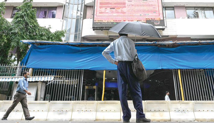 Maharashtra : A pedestrian watches share prices on a digital broadcast as he stands outside the Bombay Stock Exchange (BSE) in Mumbai on Wednesday.
