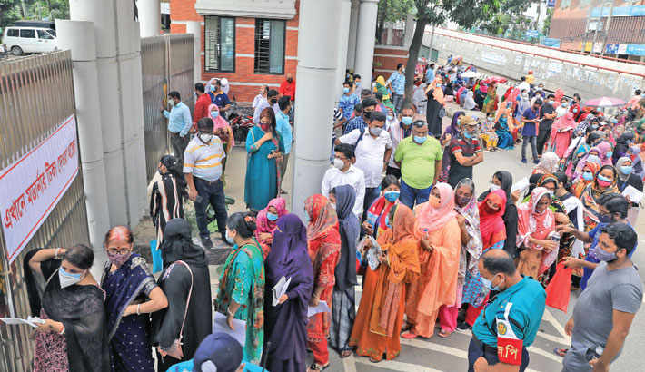 Without maintaining social distancing, people wait in queues for Covid-19 vaccine in front of the Central Police Hospital in the capital's Rajarbagh area on Thursday. —SUN photo