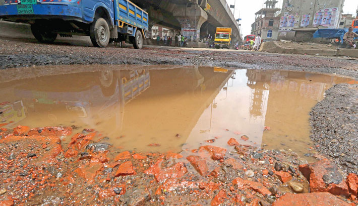 Mud, potholes and waterlogging turn a busy road in the capital's Jatrabari area unbearable. A brief rain just made the street a death trap. The snap was taken on Thursday. — MD NASIR UDDIN