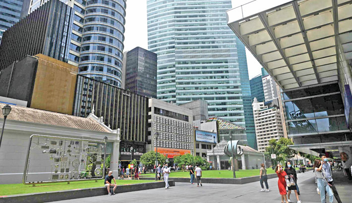 Office workers walk out during their lunch break at Raffles Place financial business district in Singapore on Thursday.