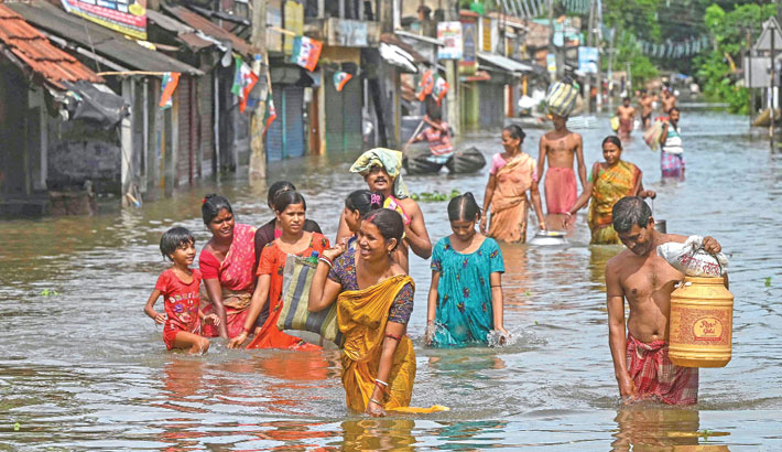 People wade through a waterlogged street in the flood hit city of Amta in the Howrah district about 65 kms from Kolkata on Thursday. —AFP PHOTO
