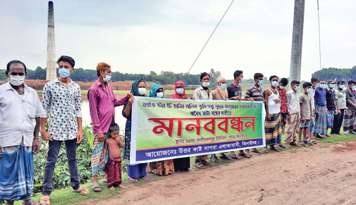 People from all walks of life form a human chain at Uttar Custsagra village in Jhenaidah Sadar Upazila on Wednesday, demanding closure of illegal brick kilns and stoppage of sand lifting in the locality.– Sun Photo