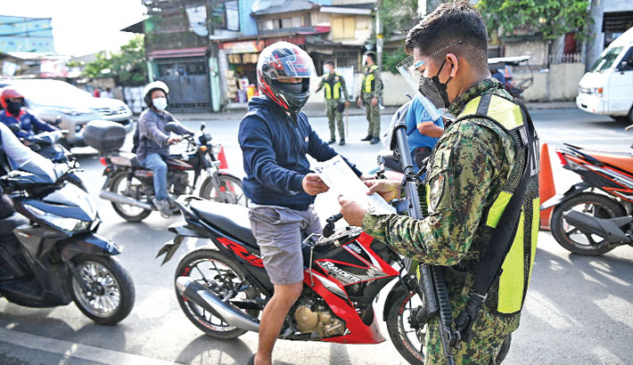 A policeman checks documents of motorists at a border check point in Marikina City, suburban Manila on Friday, after Philippines' authorities imposed another lockdown to slow the spread of the hyper-contagious Delta variant. —AFP Photo