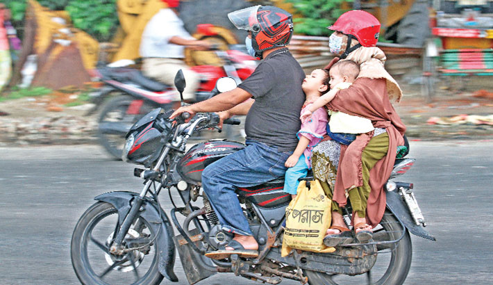 Members of a family riding a motorcycle are entering Chattogram city from a distant place amid risk of accidents. Public transport remains suspended due to the countrywide lockdown imposed to check further spread of the coronavirus. The photo was taken from Mariner's Road area in the port city on Saturday.—Rabin chowdhury