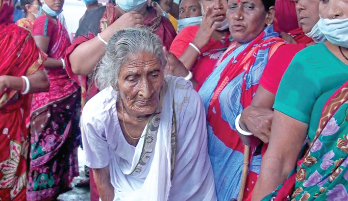 An elderly woman is waiting along with many others to get corona vaccine outside an inoculation centre at Karpara union under Sadar upazila of Gopalganj district as the mass corona vaccination programme starts across the country on Saturday.  – Sun Photo