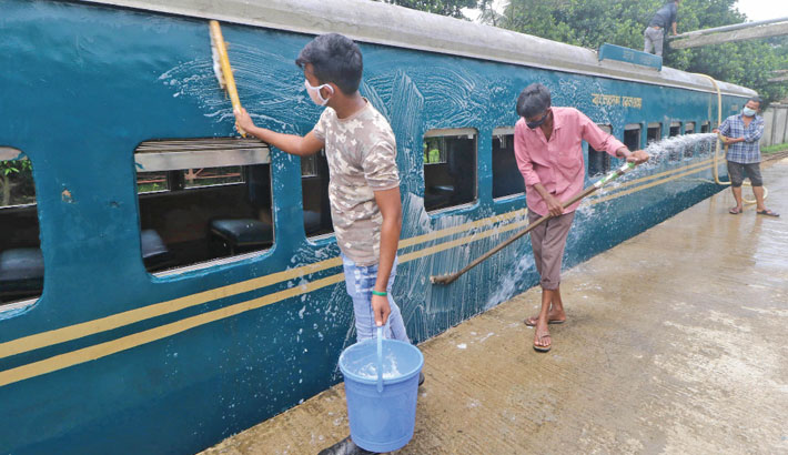 Workers busy cleaning bogies of a passenger train at Kamalapur Railway Station in the capital on Monday as the Bangladesh Railway authorities are set to resume operations tomorrow after a lockdown induced break. —SUN photo