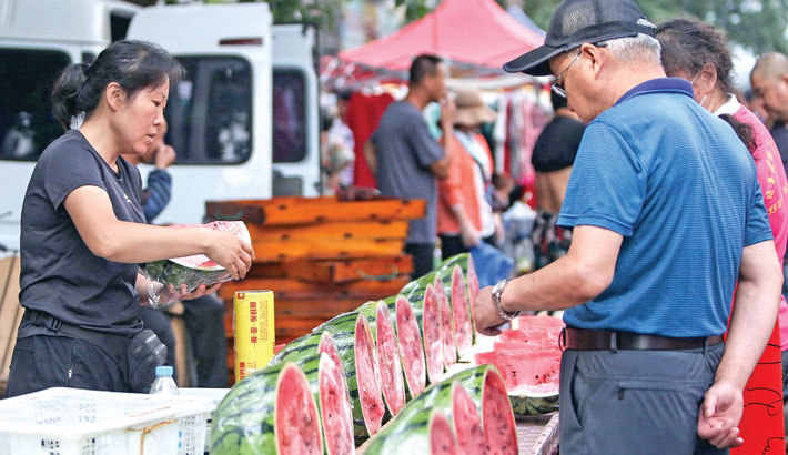 Customers buy watermelons at a market in Shenyang, in China's northeastern Liaoning province on Monday.