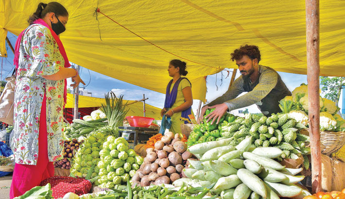 Customers buy vegetables at a vegetable market in Bangalore on Monday.