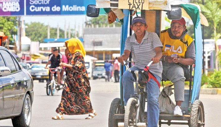 A man rides a traditional tricycle taxi in Maracaibo, Zulia State, Venezuela, recently. Franklin relies on the wind to power his small sailboat. Manuel, a former bus driver, carries passengers in a