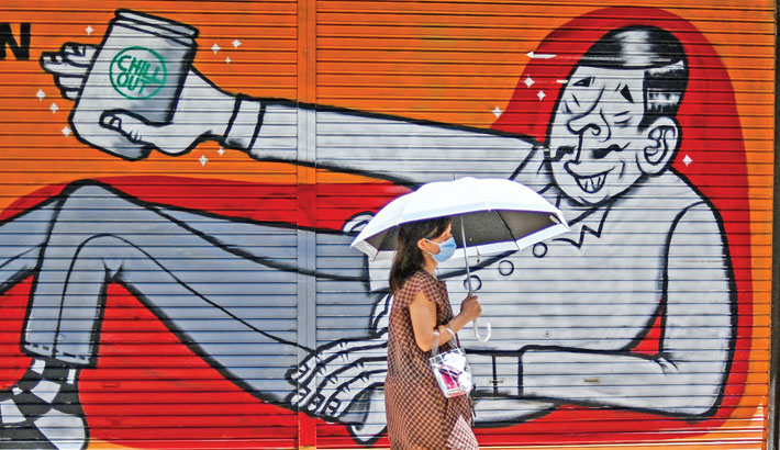 A woman walks past a closed shop in Tokyo on Tuesday.