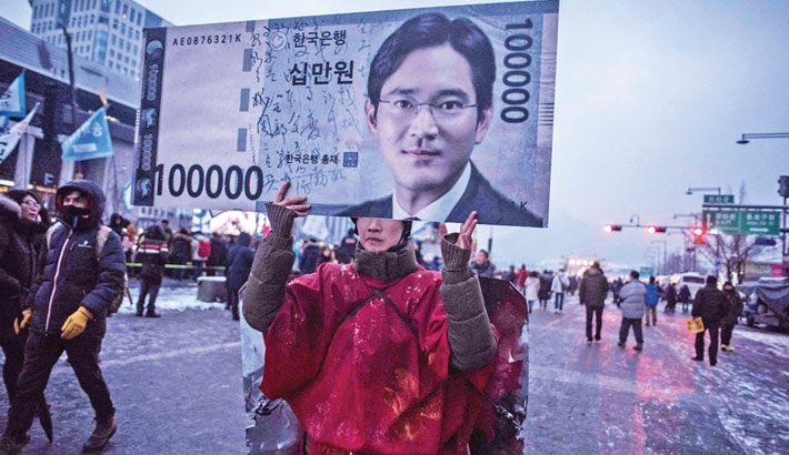 This file photo taken recently shows a protester carrying a placard showing an image of Samsung's then-heir Lee Jae-yong during an anti-government protest in Seoul. The life of soon-to-be-released Samsung chief and South Korean billionaire Lee Jae-yong epitomises the privileges, power and perils of the super-rich in the world's 12th largest economy, a country sometimes dubbed the