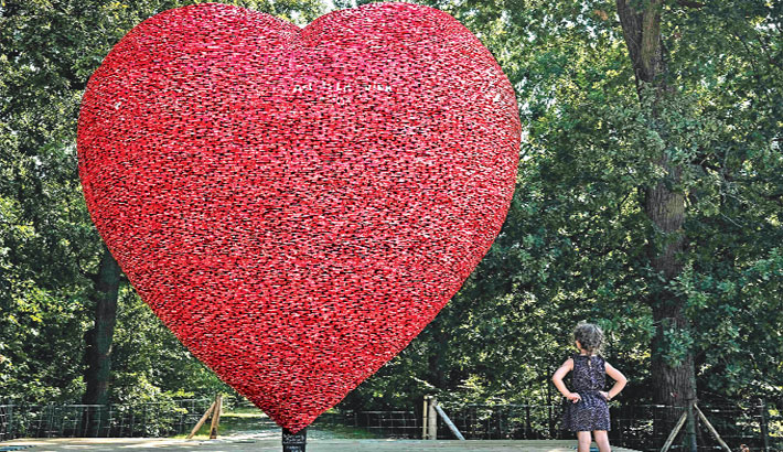A little girl looks at an artpiece, a heart made with recycled aluminium cans by Italian-Belgian artist Alfredo Longo displayed in a public park to raise awareness about climate change in Bordeaux, France, on Tuesday. — AFP PHOTO