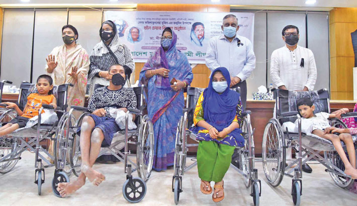 Children with disabilities pose for a photo with Home Minister Asaduzzaman Khan Kamal and Education Minister Dr Dipu Moni after receiving wheelchairs at a function in the capital on Thursday, marking the 91st birth anniversary of Bangamata Sheikh Fazilatunnesa Mujib. Bangladesh  Mohila Awami League arranged the event.