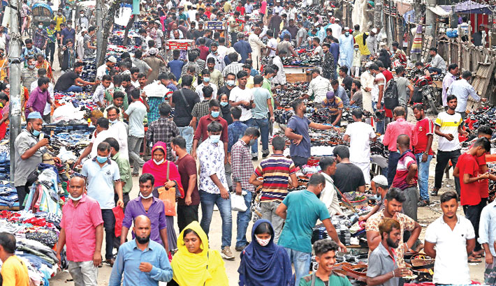 People throng makeshift shops on a road and its footpath in the capital's Gulistan area on Friday without maintaining health guidelines, including wearing face masks, amid risk of coronavirus infections after the relaxation of the  countrywide lockdown. – Reaz Ahmed Sumon