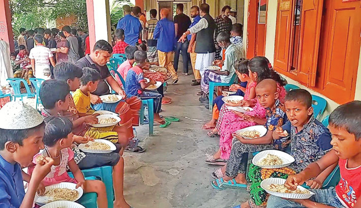 Cooked food is distributed among destitute people in Tungipara upazila of Gopalganj district on Sunday, marking the 46th martyrdom anniversary of Father of the Nation Bangabandhu Sheikh Mujibur Rahman. —sun photo
