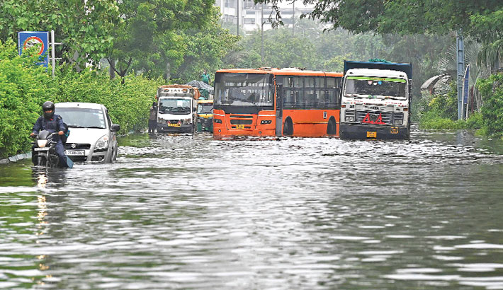 Stranded vehicles are seen on a waterlogged road after a heavy rainfall in Delhi on Saturday. — AFP PHOTO