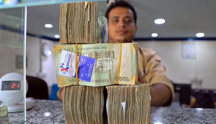 An employee displays stacks of Yemeni riyal banknotes at a currency exchange office in Yemen's capital Sanaa recently.