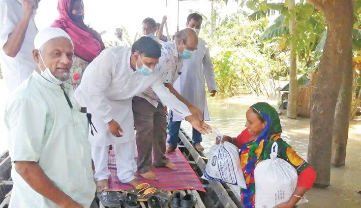 Lalpur Upazila Parishad Chairman Md Esahaque Ali distributes relief goods among flood-affected people in Padmar Char area of the upazila in Natore district on Sunday.– Sun Photo