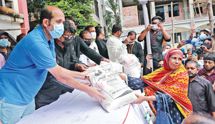 DNCC Mayor Atiqul Islam distributes foods among the destitute on Uttar Kafrul High School premises in the capital on Monday, marking National Mourning Day. —SUN PHOTO