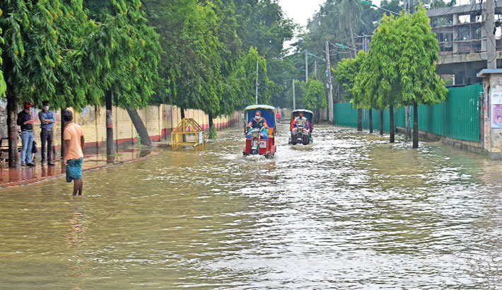 Waterlogging caused by heavy rain hampers life in different parts of Rajshahi city. The photo shows battery-run auto rickshaws are moving through waterlogged Parjatan Motel Road in the city on Monday. – Star Mail