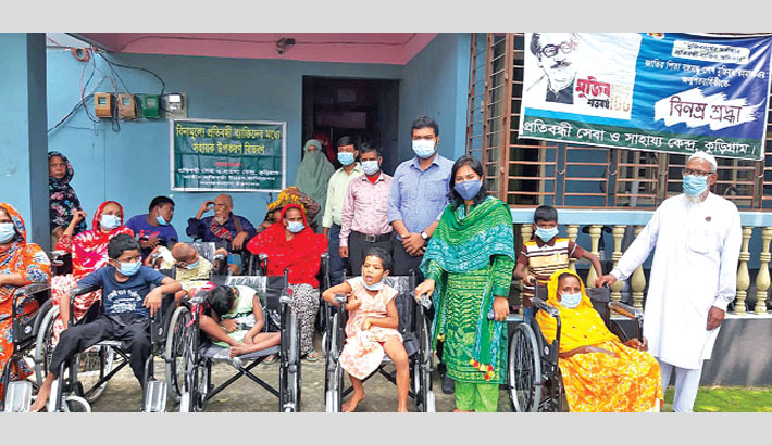 Kurigram Sadar Upazila Nirbahi Officer (UNO) Nilufa Yeasmin distributes wheelchairs and others materials among physically-challenged people on the premises of the Disability Services and Assistance Center in Kurigram on Wednesday. – Sun Photo