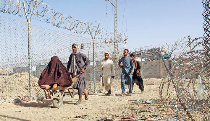 Afghans walk along a fenced corridor after crossing into Pakistan through the Pakistan-Afghanistan border crossing point in Chaman on Friday following the Taliban's stunning military takeover of Afghanistan. — AFP Photo