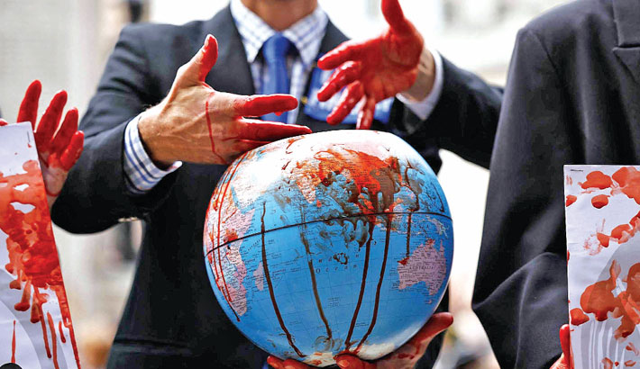 Climate activists from the Extinction Rebellion group with fake blood on their hands and a globe demonstrate outside the Bank of England in the City of London on Friday during the group's 'Impossible Rebellion' series of actions. —AFP Photo