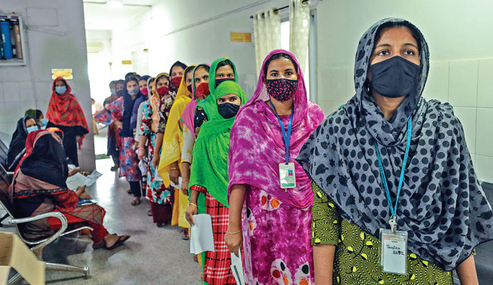 Garment workers of Chattogram EPZ factories stand in a queue to take Covid-19 jab at a vaccination programme under the supervision of Chattogram City Corporation in the port city's EPZ area on Saturday. —SUN PHOTO