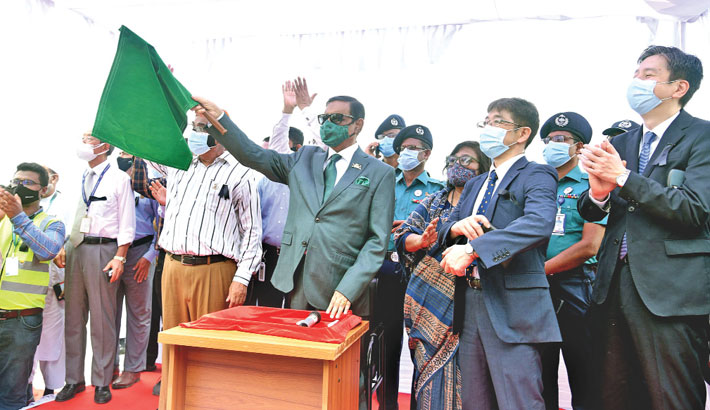 Road Transport and Bridges Minister Obaidul Quader, also Awami League general secretary, on Sunday waves a flag at the inaugural ceremony of performance test of first metro-rail on viaduct at Uttara's Diabari depot. —SUN photo
