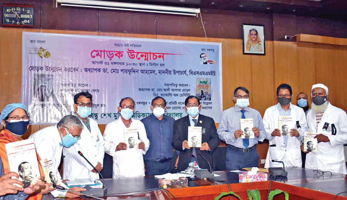 BSMMU Vice-Chancellor Prof Dr Md Sharfuddin Ahmed along with others holds the copy of a book titled Bangabandhur Swasthya Bhabna (Bangabandhu's Thoughts on Health) on the university premises on Tuesday.