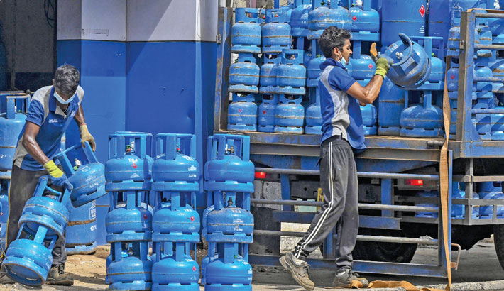 Labourer loads gas canisters onto a truck in Colombo on Tuesday following Sri Lanka's declaration of state of emergency over food shortages as private banks ran out of foreign exchange to finance imports.
